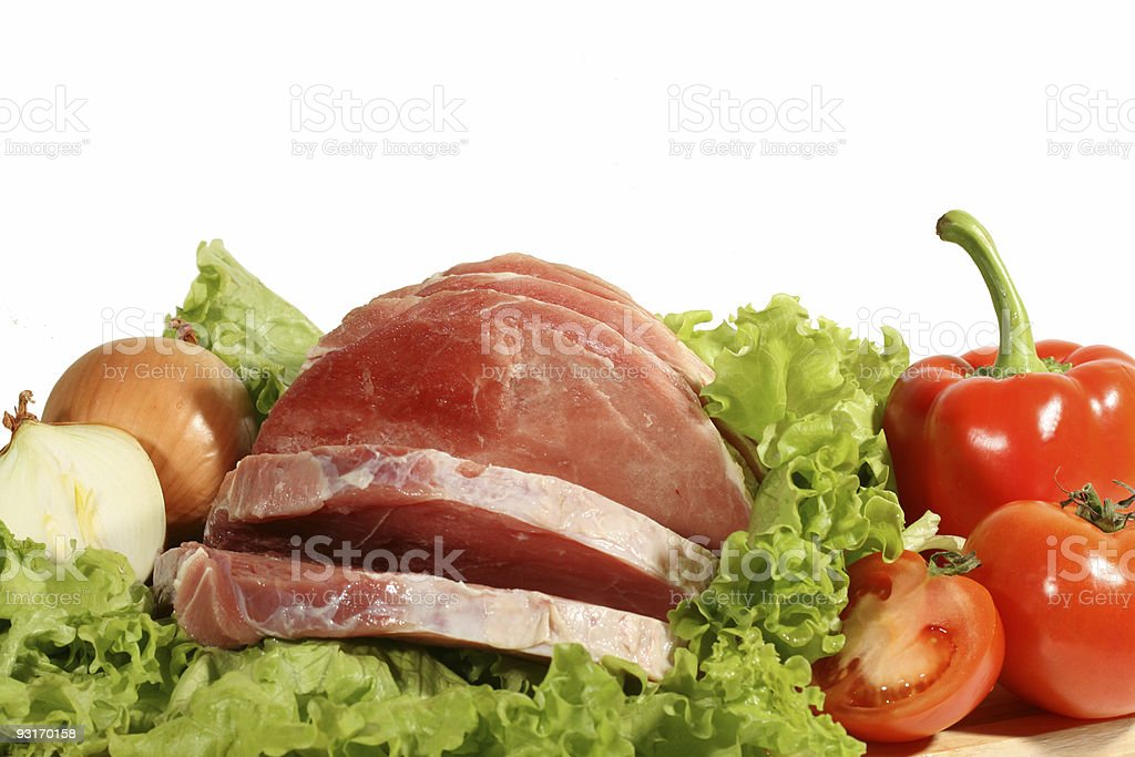 Fresh meat on leaves of salad with vegetables royalty-free stock photo