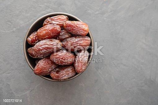 978314900 istock photo Fresh Medjool Dates in a bowl. Ramadan kareem. Black background. Top view. Copy space. 1022721014