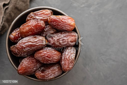978314900 istock photo Fresh Medjool Dates in a bowl. Ramadan kareem. Black background. Top view. Copy space. 1022721034