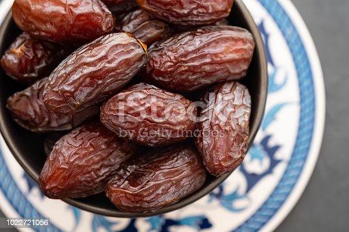 978314900 istock photo Fresh Medjool Dates in a bowl. Ramadan kareem. Black background. Top view. Copy space. 1022721056