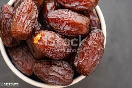 978314900 istock photo Fresh Medjool Dates in a bowl. Ramadan kareem. Black background. Top view. Copy space. 1022721078