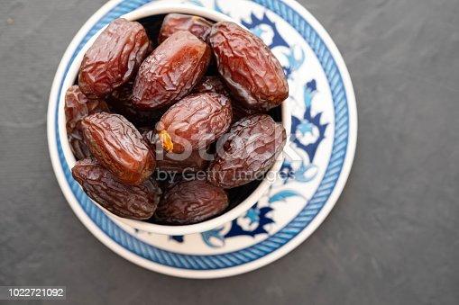 978314900 istock photo Fresh Medjool Dates in a bowl. Ramadan kareem. Black background. Top view. Copy space. 1022721092