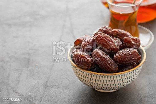 978314900 istock photo Fresh Medjool Dates in a bowl. Ramadan kareem. Black background. Top view. Copy space. 1022723382