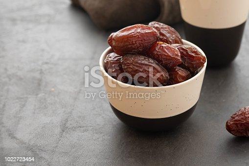 978314900 istock photo Fresh Medjool Dates in a bowl. Ramadan kareem. Black background. Top view. Copy space. 1022723454