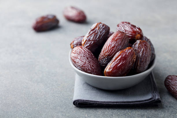 Fresh medjool dates in bowl. Grey background. Copy space. stock photo