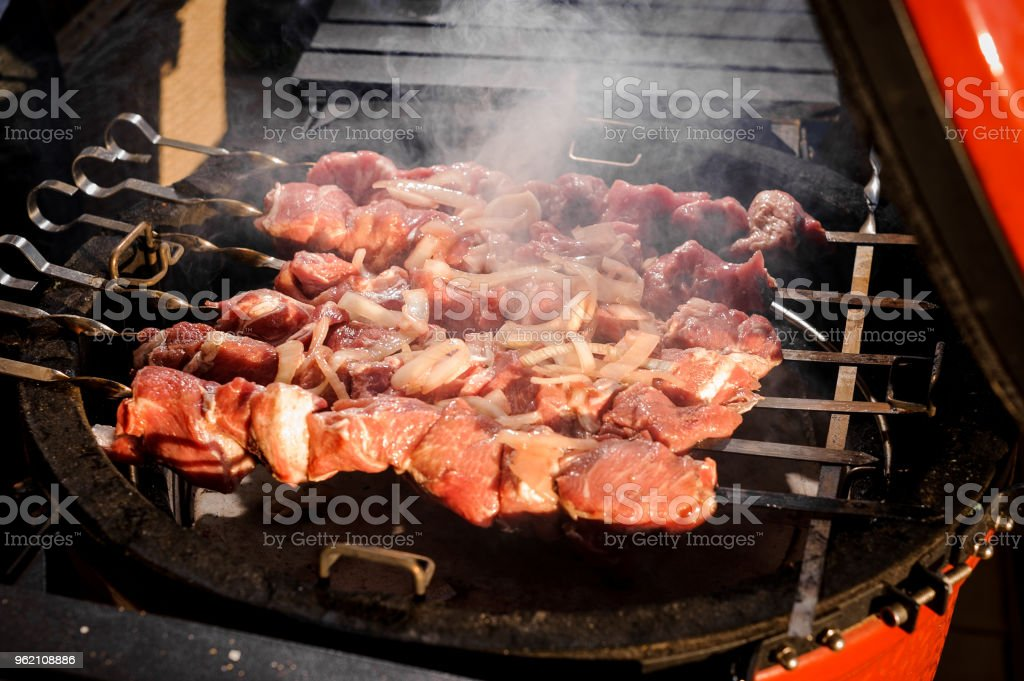 Fresh meet stringed on the steel skewers and cooked on the barbecue grill stock photo