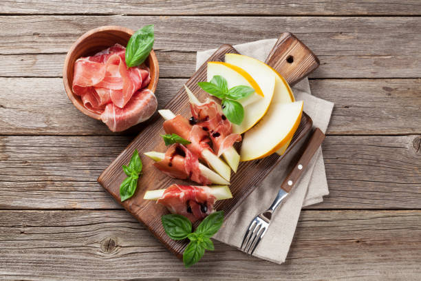 Fresh melon with prosciutto and basil stock photo