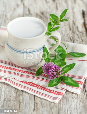 Fresh milk in ceramic mug and clover flower on the old table