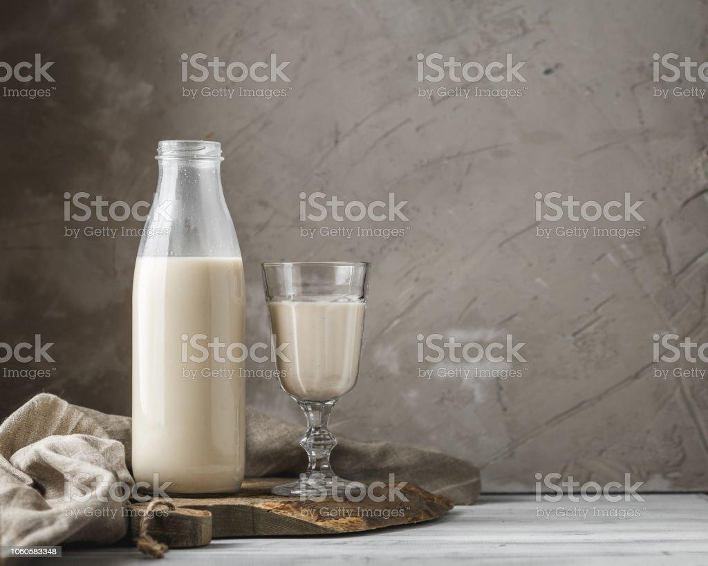 Reusable glass bottle of fresh milk on rustic background