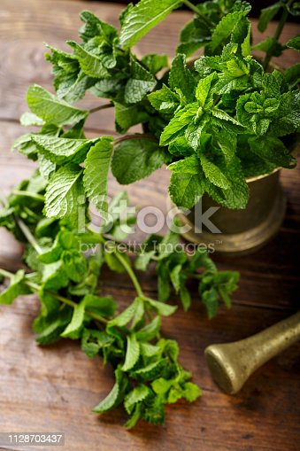 istock Fresh mint in a brass mortar on a brown wooden background. 1128703437