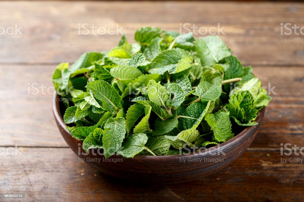 Fresh mint on a wooden background, in a dark brown clay plate royalty-free stock photo