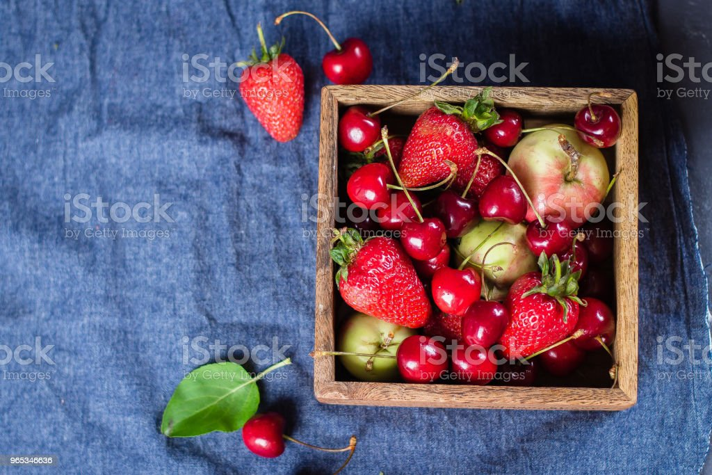 Fresh mix of berries in a wooden box on blue denim background. Copy space. Summer Berries and Fruits - strawberry, cherry and apples. Top view royalty-free stock photo