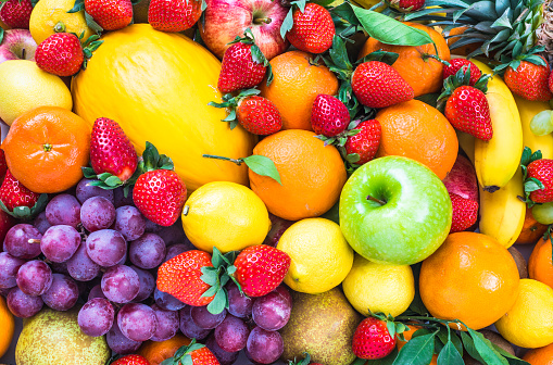 Fresh mixed fruits background.Organic fruits multicolore background.