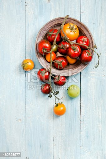 Fresh mixed tomatoes in a bowl on wooden table