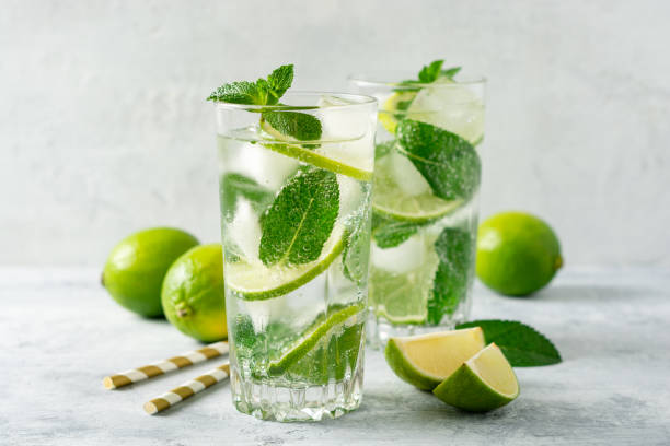 Fresh mojito cocktail with lime and mint in glass on concrete background. Cold refreshing drink. Fresh mojito cocktail with lime and mint in glass on concrete background. Cold refreshing drink. Selective focus. mojito stock pictures, royalty-free photos & images