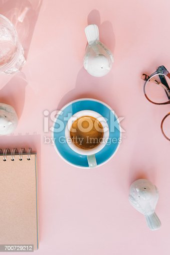 istock Fresh morning espresso coffee with a beautiful thick crema, glasses, paper notebook, laptop green ceramic decorative birds on the pink background. Flat lay 700729212
