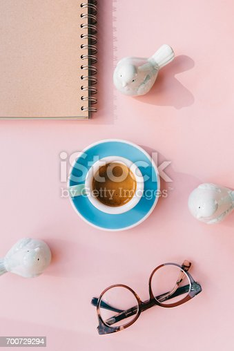 istock Fresh morning espresso coffee with a beautiful thick crema, glasses, paper notebook, laptop green ceramic decorative birds on the pink background. Flat lay 700729294