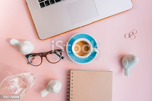 istock Fresh morning espresso coffee with a beautiful thick crema, glasses, paper notebook, laptop green ceramic decorative birds on the pink background. Flat lay 700729358
