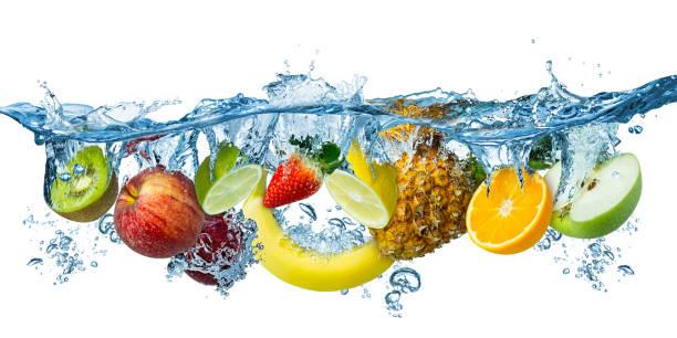 frutas múltiples frescas salpicando en agua azul claro salpicadero de alimentos saludables concepto de frescura dieta de fondo blanco aislado - fruta fotografías e imágenes de stock
