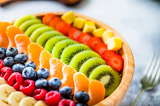 High angle view closeup of a wooden bowl full of fresh multicolored fruits like mango, strawberries, kiwi fruit, tangerine, blueberries, raspberries and banana. Fruits are disposed in a row by types. Studio shot taken with Canon EOS 6D Mark II and Canon EF 24-105 mm f/4L