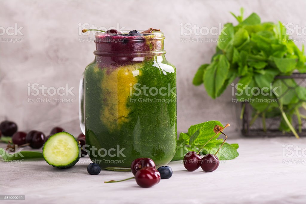 Fresh multicolored smoothie over stone table stock photo