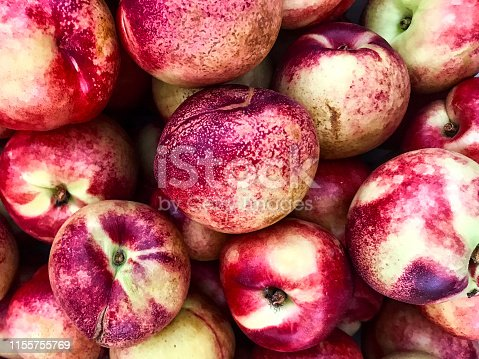This is a close-up photograph of a bunch of nectarines from a farmers market