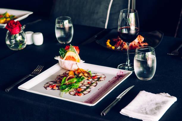 frischer tintenfisch carpacio mit zitrusfrüchten spinat salat pesto balsamico-dressing, feine wohn / tischdekoration im restaurant - carpaccio salat stock-fotos und bilder
