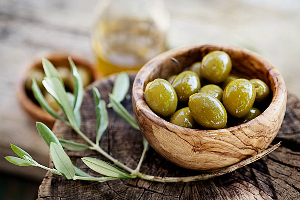 Fresh olives Fresh olives and olive oil  on rustic wooden background. Olives in olive wood. olives stock pictures, royalty-free photos & images