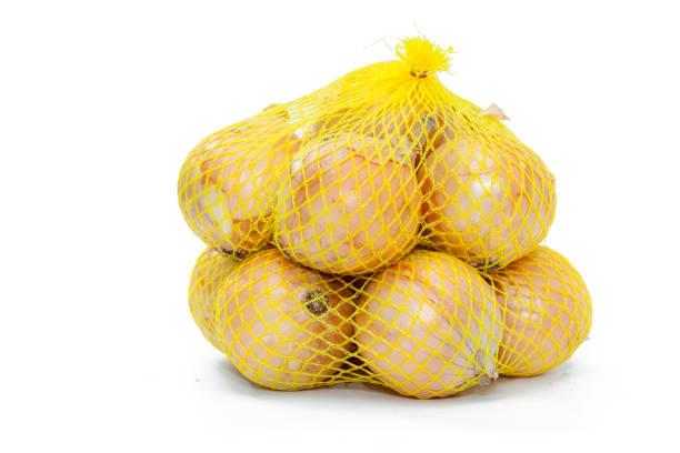 노란색 플라스틱 그물에 신선한 양파 스톡 사진