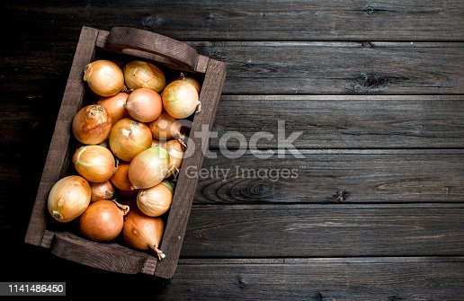 Fresh onions in the box. On wooden background