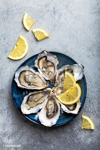 Set of half dozen fresh opened oysters in shell with lemon wedges served on rustic blue plate on gray stone background, close up, top view