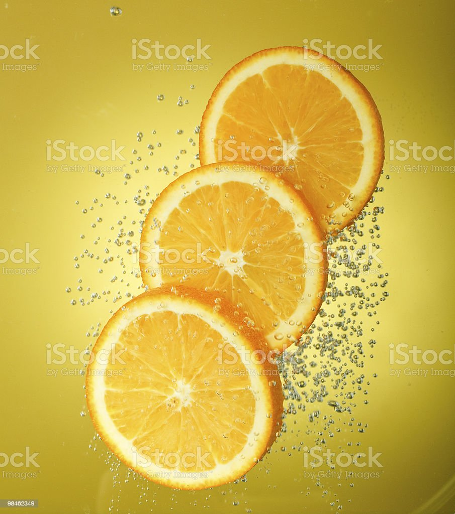 Fresh orange dropped into water with bubbles royalty-free stock photo