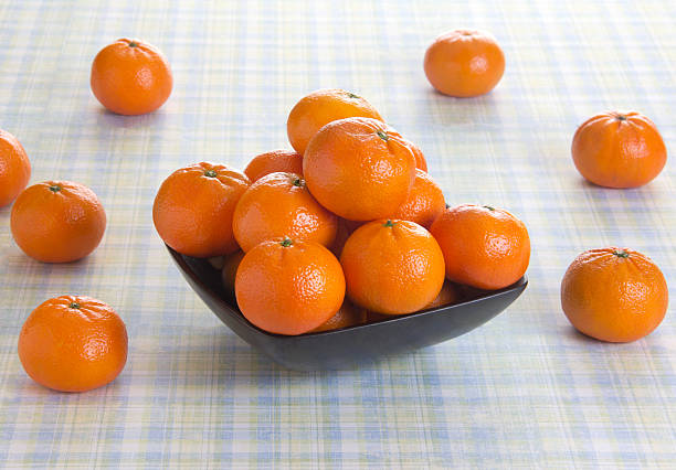 Fresh orange fruits in a bowl placed on a table stock photo