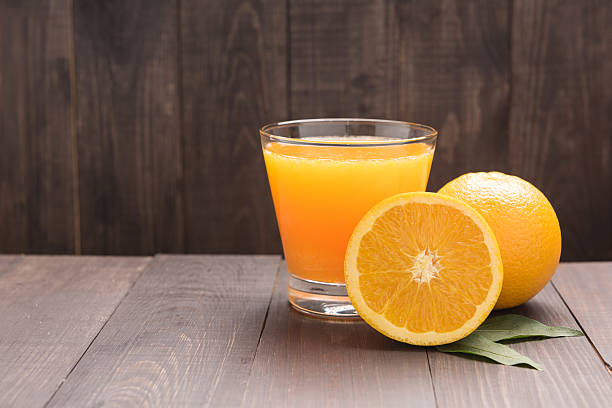 Fresh orange juice and oranges on wooden table stock photo