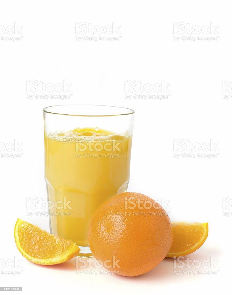Fresh orange juice in a glass next to fresh oranges stock photo
