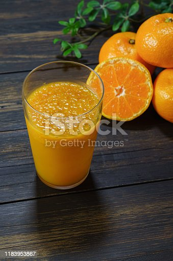 Fresh orange juice in glass isolated on wooden background