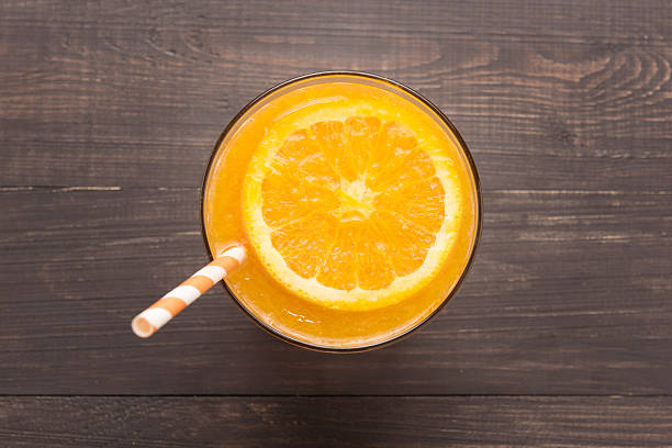 Fresh orange juice in glass on wooden background stock photo