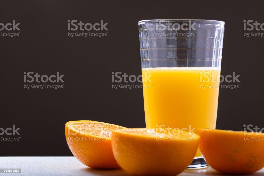 Verse jus d'orange in glas met oranje gesneden in helften zijaanzicht op donkere achtergrond - Royalty-free Antioxidant Stockfoto
