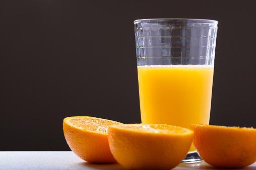 Verse Jus Dorange In Glas Met Oranje Gesneden In Helften Zijaanzicht Op Donkere Achtergrond Stockfoto en meer beelden van Antioxidant