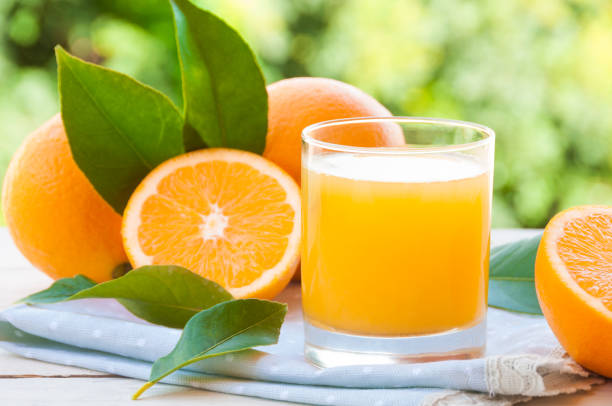 Fresh orange juice with oranges and leaves outdoors stock photo