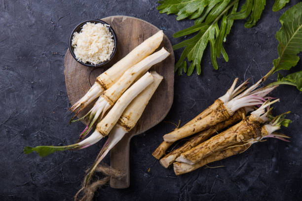Fresh orgaanic horseradish or Horse-radish root on wooden cutting board.  top view Fresh orgaanic horseradish or Horse-radish root on wooden cutting board.  top view horseradish stock pictures, royalty-free photos & images