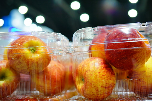 Fresh organic apples in plastic box packing at market