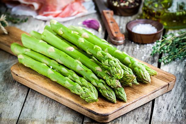 Fresh organic asparagus on a cutting board with Parma ham stock photo