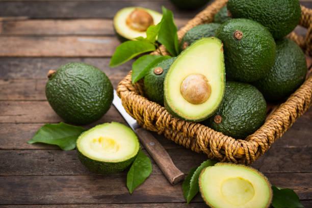 abacate orgânico fresco na tabela de madeira - abacate - fotografias e filmes do acervo