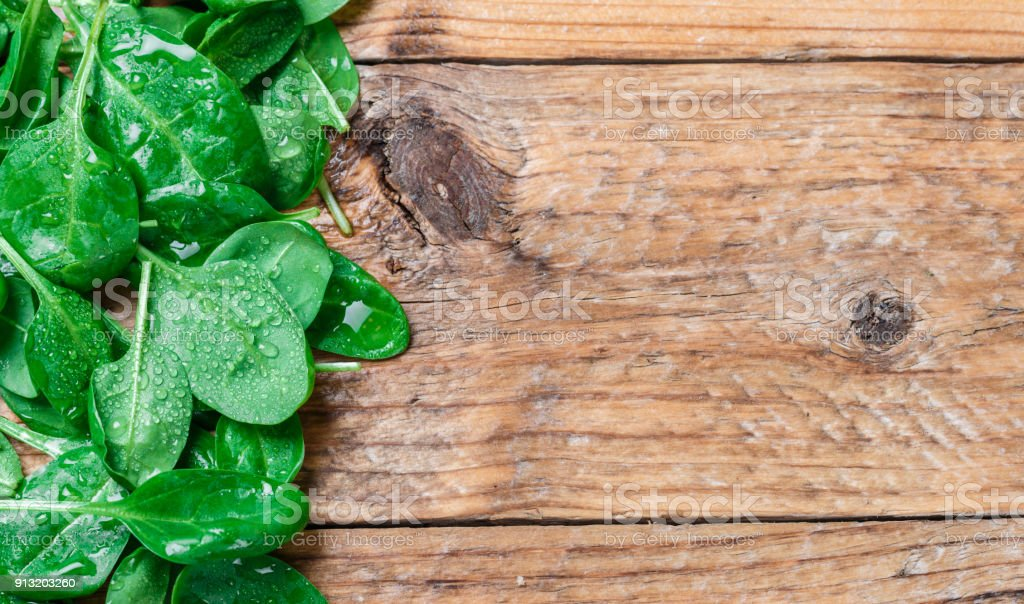 Fresh organic baby spinach with water drops on the old wooden table. Selective focus and copy space stock photo