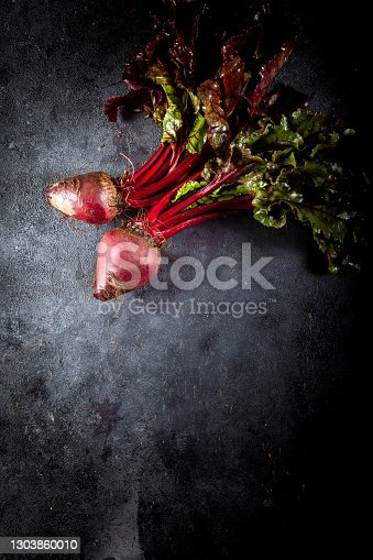 istock Fresh organic beet, beetroot on dark background. Copy space. Top view. Beetroot with herbage on dark background. 1303860010