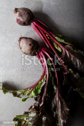 istock Fresh organic beet, beetroot. Top view. Beetroot with herbage on brown stone background. 1303818203