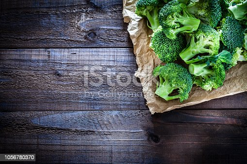 Fresh organic broccoli on crumpled brown paper arranged at the top-right corner of an old weathered wooden table. Useful copy space left for text and/or logo. Predominant colors are green and brown. Low key DSRL studio photo taken with Canon EOS 5D Mk II and Canon EF 100mm f/2.8L Macro IS USM.