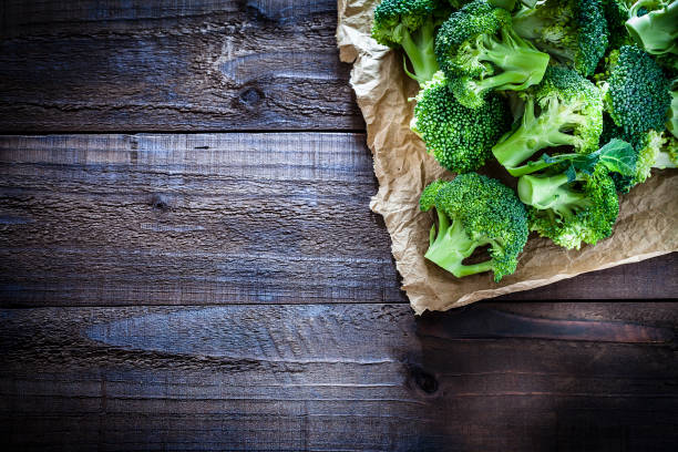 Fresh organic broccoli on crumpled brown paper still life Fresh organic broccoli on crumpled brown paper arranged at the top-right corner of an old weathered wooden table. Useful copy space left for text and/or logo. Predominant colors are green and brown. Low key DSRL studio photo taken with Canon EOS 5D Mk II and Canon EF 100mm f/2.8L Macro IS USM. broccoli stock pictures, royalty-free photos & images
