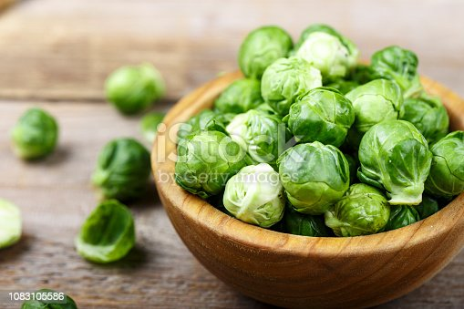 fresh organic brussels sprouts raw in a plate on wooden background. space for text